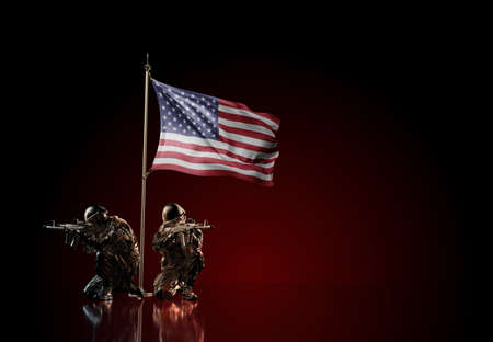 Concept of military conflict with soldier statues and waving national flag of United States. Illustration of coup idea. Two guards defending the symbol of country against red wall Reklamní fotografie