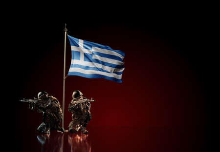 Concept of military conflict with soldier statues and waving national flag of Greece. Illustration of coup idea. Two guards defending the symbol of country against red wall Reklamní fotografie