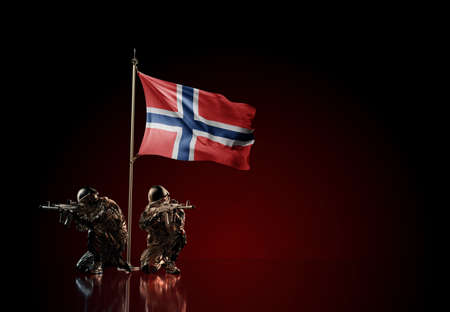 Concept of military conflict with soldier statues and waving national flag of Svalbard and Jan Mayen. Illustration of coup idea. Two guards defending the symbol of country against red wall