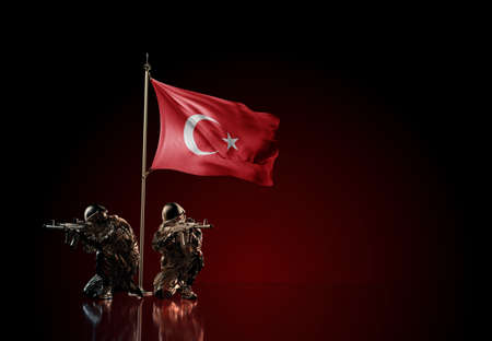 Concept of military conflict with soldier statues and waving national flag of Turkey. Illustration of coup idea. Two guards defending the symbol of country against red wall