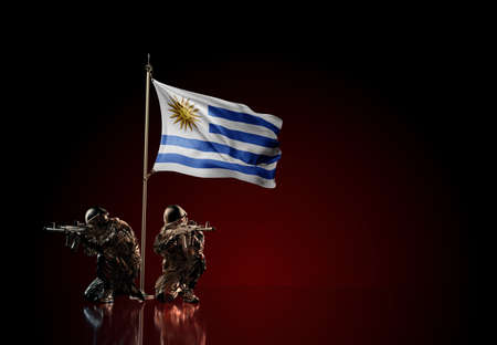 Concept of military conflict with soldier statues and waving national flag of Uruguay. Illustration of coup idea. Two guards defending the symbol of country against red wall