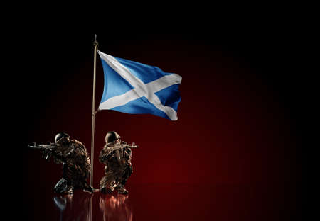 Concept of military conflict with soldier statues and waving national flag of Scotland. Illustration of coup idea. Two guards defending the symbol of country against red wall Reklamní fotografie