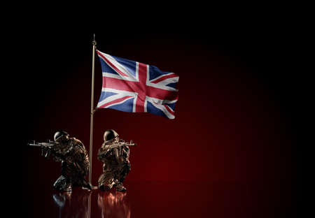 Concept of military conflict with soldier statues and waving national flag of United Kingdom. Illustration of coup idea. Two guards defending the symbol of country against red wall