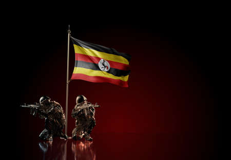 Concept of military conflict with soldier statues and waving national flag of Uganda. Illustration of coup idea. Two guards defending the symbol of country against red wall