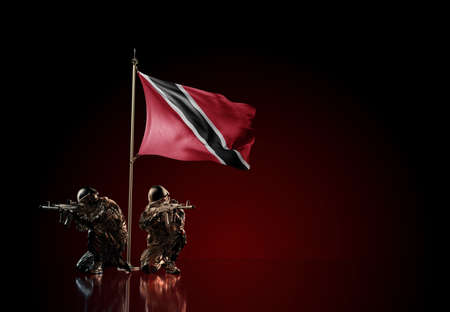 Concept of military conflict with soldier statues and waving national flag of Trinidad and Tobago. Illustration of coup idea. Two guards defending the symbol of country against red wall Reklamní fotografie