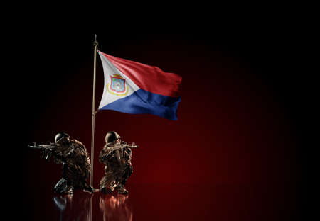 Concept of military conflict with soldier statues and waving national flag of Sint Maarten. Illustration of coup idea. Two guards defending the symbol of country against red wall