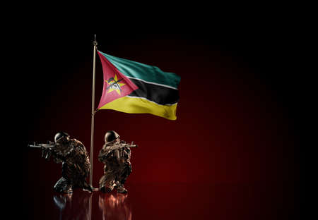 Concept of military conflict with soldier statues and waving national flag of Mozambique. Illustration of coup idea. Two guards defending the symbol of country against red wall