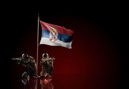 Concept of military conflict with soldier statues and waving national flag of Serbia. Illustration of coup idea. Two guards defending the symbol of country against red wall