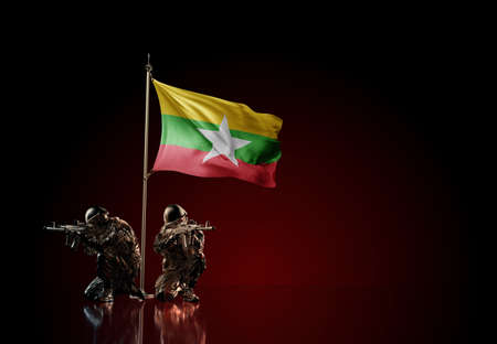 Concept of military conflict with soldier statues and waving national flag of Myanmar. Illustration of coup idea. Two guards defending the symbol of country against red wall
