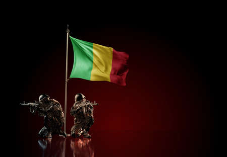 Concept of military conflict with soldier statues and waving national flag of Mali. Illustration of coup idea. Two guards defending the symbol of country against red wall