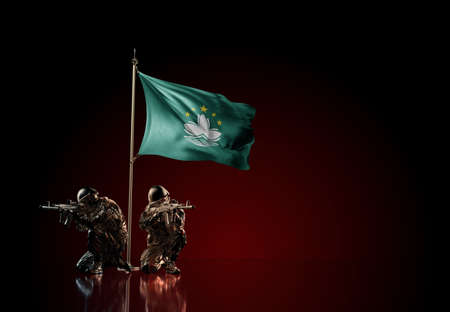 Concept of military conflict with soldier statues and waving national flag of Macau. Illustration of coup idea. Two guards defending the symbol of country against red wall