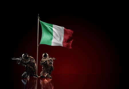 Concept of military conflict with soldier statues and waving national flag of Italy. Illustration of coup idea. Two guards defending the symbol of country against red wall