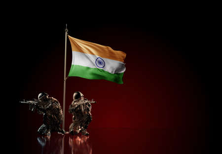 Concept of military conflict with soldier statues and waving national flag of India. Illustration of coup idea. Two guards defending the symbol of country against red wall