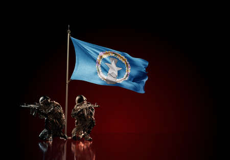 Concept of military conflict with soldier statues and waving national flag of Northern Mariana Islands. Illustration of coup idea. Two guards defending the symbol of country against red wall Reklamní fotografie