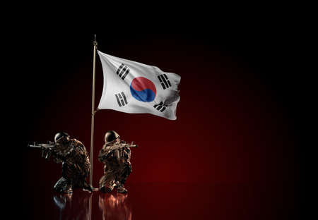 Concept of military conflict with soldier statues and waving national flag of South Korea. Illustration of coup idea. Two guards defending the symbol of country against red wall