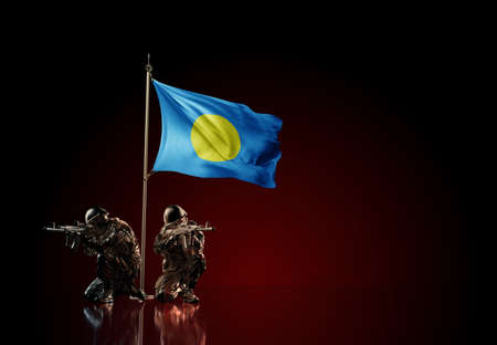 Concept of military conflict with soldier statues and waving national flag of Palau. Illustration of coup idea. Two guards defending the symbol of country against red wall