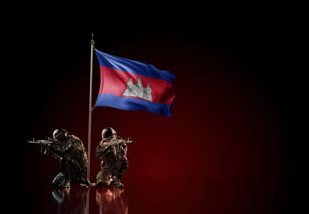 Concept of military conflict with soldier statues and waving national flag of Cambodia. Illustration of coup idea. Two guards defending the symbol of country against red wall