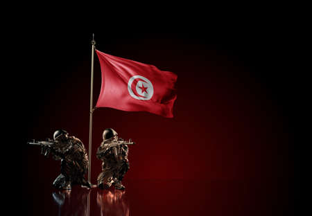 Concept of military conflict with soldier statues and waving national flag of Tunisia. Illustration of coup idea. Two guards defending the symbol of country against red wall