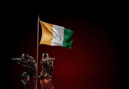 Concept of military conflict with soldier statues and waving national flag of Ivory Coast. Illustration of coup idea. Two guards defending the symbol of country against red wall