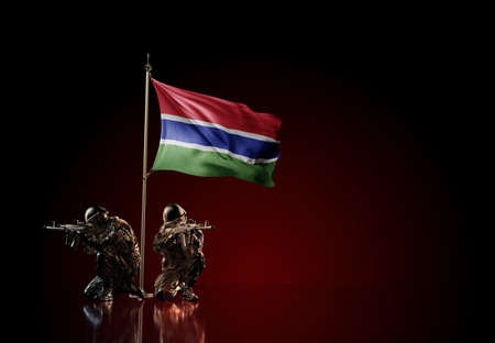 Concept of military conflict with soldier statues and waving national flag of Gambia. Illustration of coup idea. Two guards defending the symbol of country against red wall