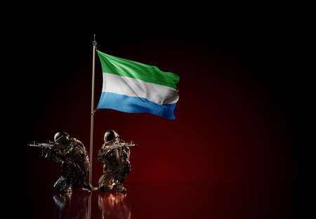 Concept of military conflict with soldier statues and waving national flag of Sierra Leone. Illustration of coup idea. Two guards defending the symbol of country against red wall