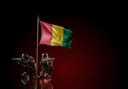 Concept of military conflict with soldier statues and waving national flag of Guinea. Illustration of coup idea. Two guards defending the symbol of country against red wall