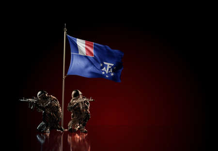 Concept of military conflict with soldier statues and waving national flag of French Southern and Antarctic Lands. Illustration of coup idea. Two guards defending the symbol of country against red wall Reklamní fotografie