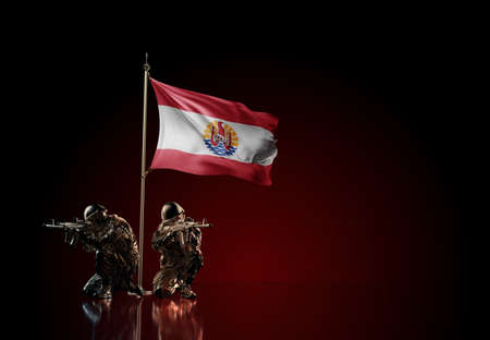 Concept of military conflict with soldier statues and waving national flag of French Polynesia. Illustration of coup idea. Two guards defending the symbol of country against red wall Reklamní fotografie