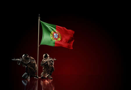 Concept of military conflict with soldier statues and waving national flag of Portugal. Illustration of coup idea. Two guards defending the symbol of country against red wall