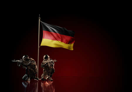 Concept of military conflict with soldier statues and waving national flag of Germany. Illustration of coup idea. Two guards defending the symbol of country against red wall Reklamní fotografie
