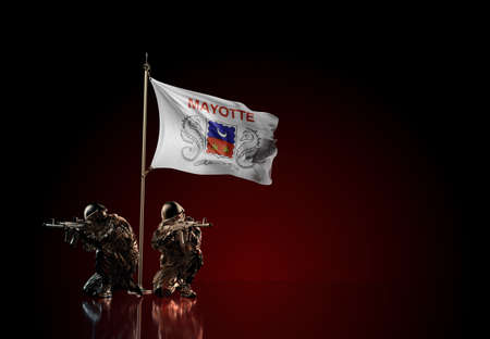 Concept of military conflict with soldier statues and waving national flag of Mayotte. Illustration of coup idea. Two guards defending the symbol of country against red wall Reklamní fotografie