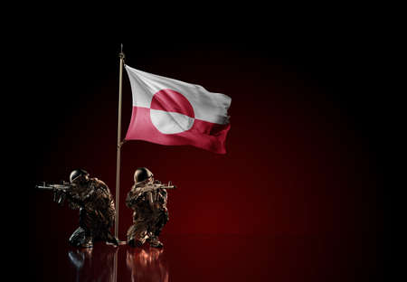 Concept of military conflict with soldier statues and waving national flag of Greenland. Illustration of coup idea. Two guards defending the symbol of country against red wall