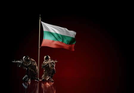 Concept of military conflict with soldier statues and waving national flag of Bulgaria. Illustration of coup idea. Two guards defending the symbol of country against red wall