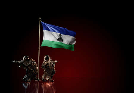 Concept of military conflict with soldier statues and waving national flag of Lesotho. Illustration of coup idea. Two guards defending the symbol of country against red wall Reklamní fotografie