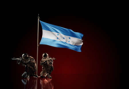 Concept of military conflict with soldier statues and waving national flag of Honduras. Illustration of coup idea. Two guards defending the symbol of country against red wall