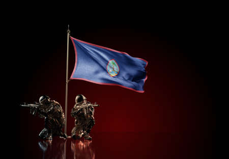 Concept of military conflict with soldier statues and waving national flag of Guam. Illustration of coup idea. Two guards defending the symbol of country against red wall
