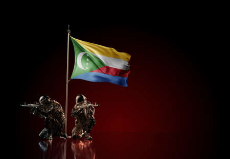 Concept of military conflict with soldier statues and waving national flag of Comoros. Illustration of coup idea. Two guards defending the symbol of country against red wall