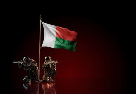 Concept of military conflict with soldier statues and waving national flag of Madagascar. Illustration of coup idea. Two guards defending the symbol of country against red wall