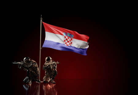 Concept of military conflict with soldier statues and waving national flag of Croatia. Illustration of coup idea. Two guards defending the symbol of country against red wall Reklamní fotografie