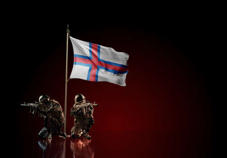 Concept of military conflict with soldier statues and waving national flag of Faroe Isnalnds. Illustration of coup idea. Two guards defending the symbol of country against red wall