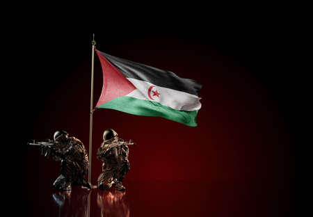 Concept of military conflict with soldier statues and waving national flag of Western Sahara. Illustration of coup idea. Two guards defending the symbol of country against red wall