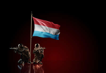 Concept of military conflict with soldier statues and waving national flag of Luxembourg. Illustration of coup idea. Two guards defending the symbol of country against red wall