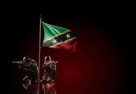 Concept of military conflict with soldier statues and waving national flag of Saint Kitts and Nevis. Illustration of coup idea. Two guards defending the symbol of country against red wall