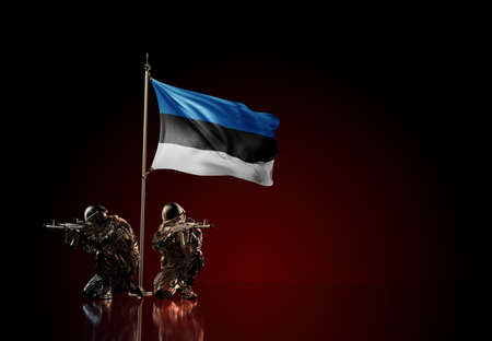Concept of military conflict with soldier statues and waving national flag of Estonia. Illustration of coup idea. Two guards defending the symbol of country against red wall