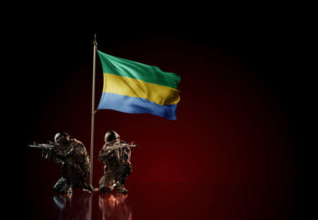 Concept of military conflict with soldier statues and waving national flag of Gabon. Illustration of coup idea. Two guards defending the symbol of country against red wall