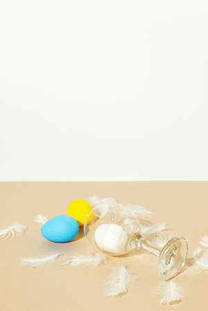 2021 Easter composition on champagne colored background. Colorful eggs with wine glass and white feathers. Creative retro minimal concept.