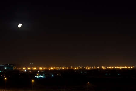 Long Exposure captures South Al Barsha city lights and moon quickly falling north east, on the upper left side of the picture. Stock Photo