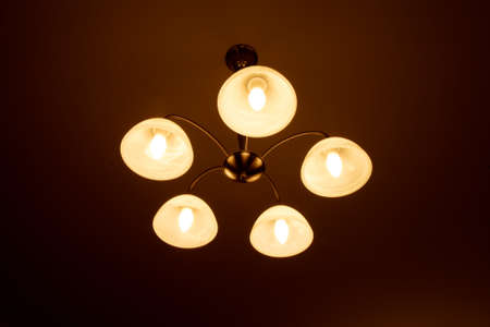 concetrated: A 5 bulb ceiling lamp showing UFO alike system of distribuiting light in a too much concetrated way.