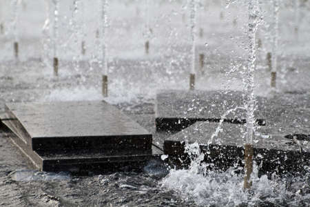 Water jets pointing upwards from a fountain.