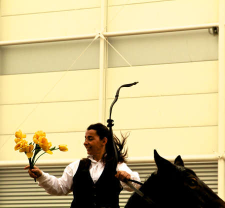 The woman who catch the flowers out of the hands man is the winning lover at Roma Cavalli horse fair in Rome, Italy on April 2011. Editorial